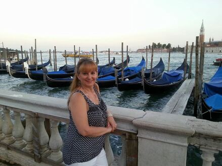 Yenesis standing in front of small boats off a dock in Italy